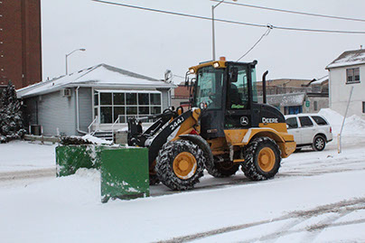 Yellow John Deere Tractor moving Snow on the Street